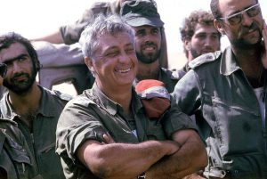 GENERAL ARIEL SHARON LAUGHING WITH HIS WARRIORS DURING THE YOM KIPPUR WAR, SINAI DESERT 1973